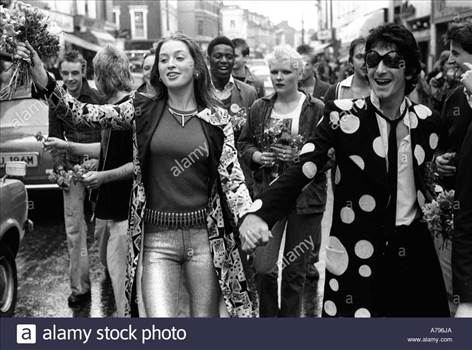 punks-hand-out-flowers-to-passing-car-drivers-as-they-walk-down-the-A796JA_zps2hffdgpo.jpg by Arthur Pringle