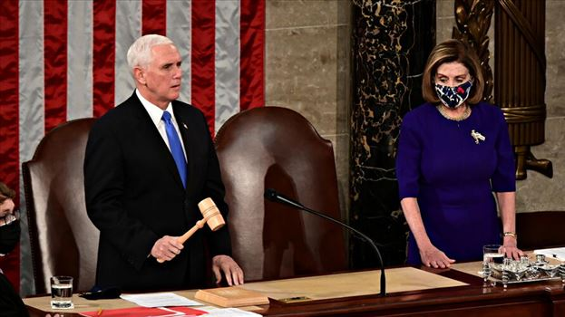 U.S. Speaker of the House Nancy Pelosi listens as U.S. Vice President Mike Pence speaks during a joint session of Congress to certify the 2020 electio by mohsen dehbashi