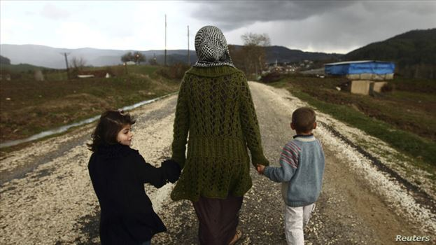Sawssan  Abdelwahab, who fled Idlib in Syria, walks with her children outside the refugees camp near the Turkish-Syrian border in the southeastern cit by mohsen dehbashi