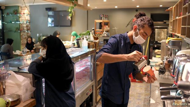 A worker wearing a protective face mask prepares a coffee at a coffee shop, following the outbreak of the coronavirus disease (COVID-19), in Tehran, I by mohsen dehbashi