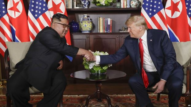 U. S. President Donald Trump shakes hands with North Korea leader Kim Jong Un during their first meetings at the Capella resort on Sentosa Island Tues by mohsen dehbashi