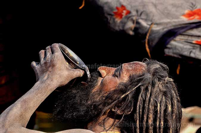 Culture- Naga Sadhu's (India) A Naga Sadhu having water at Ghats in Varanasi. by Anil Sharma Fotography