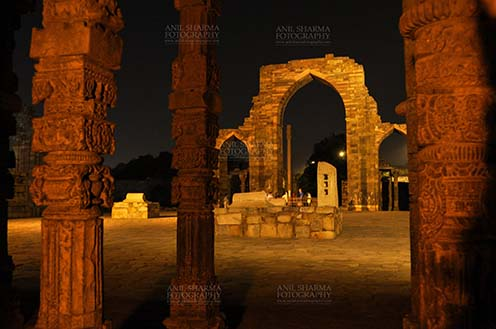 Monuments- Qutab Minar in Night, New Delhi, India. An ornately carved pillar and arches of Iltutmish screen at the Quwwat-Ul-Islam mosque in night at Qutub Minar Complex, Mehrauli , New Delhi, India. by Anil Sharma Fotography