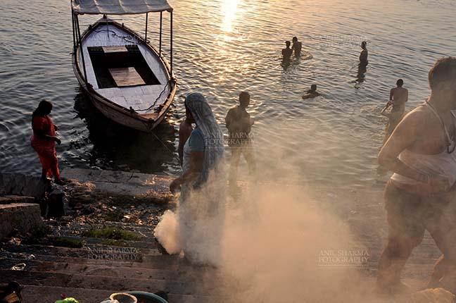 Travel- Varanasi the city of light (India) Devotees taking bath and women burning some waste material at the bank of Holy River Ganges at Varanasi, Uttar Pradesh, India. by Anil Sharma Fotography
