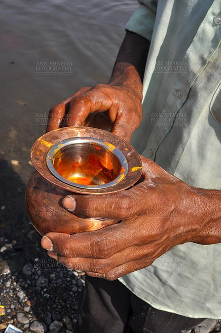 Fairs- Baneshwar Tribal Fair Baneshwar, Dungarpur, Rajasthan, India- February 14, 2011: A devotee holding saffron in a brass pot for the traditional ritual at the Baneshwar Mahadev at Baneshwar, Dungarpur, Rajasthan, India by Anil Sharma Fotography
