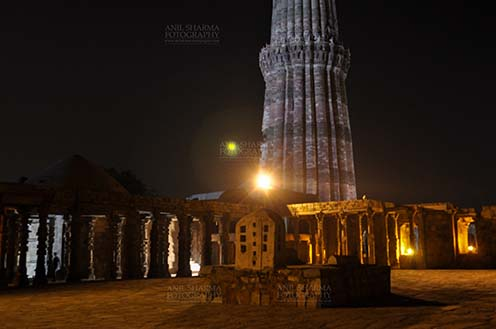 Monuments- Qutab Minar in Night, New Delhi, India. The Beauty of arches of Iltutmish screen and some tourists standing near the iron pillar in night at Qutub Minar Complex, Mehrauli , New Delhi, India. by Anil Sharma Fotography