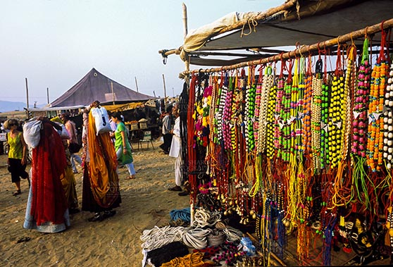 Fairs- Pushkar Fair (Rajasthan) Pushkar, Rajasthan, India- May 23, 2008: Some tourists and a necklaces, beads, jewelry, gemstones, bracelets, earrings, bangles, and devotional object shop for religious ceremonies at Pushkar fair, Rajasthan, India. by Anil Sharma Fotography