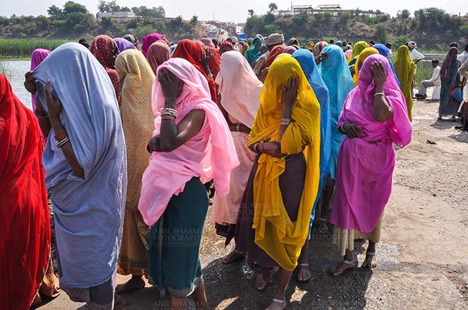 Fairs- Baneshwar Tribal Fair Baneshwar, Dungarpur, Rajasthan, India- February 14, 2011: Bhil women in brightly coloured veils and saris covering their faces ready fot the ritual bath at Baneshwar Dungarpur, Rajasthan, India. by Anil Sharma Fotography