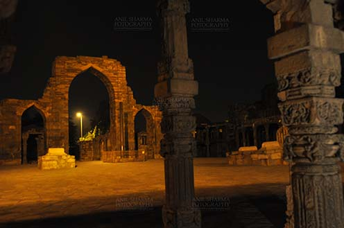 Monuments- Qutab Minar in Night, New Delhi, India. Hindu Columns with stone carving at Quwwat-Ul-Islam mosque courtyard in night at Qutub Minar Complex, New Delhi, India. by Anil Sharma Fotography