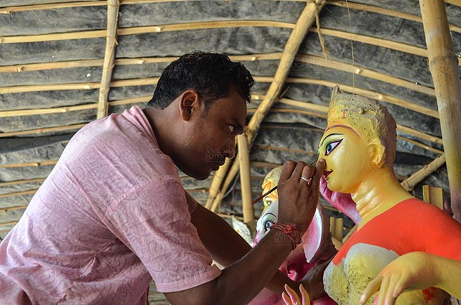 Festivals- Durga Puja Festival Durga Puja Festival, Noida, Uttar Pradesh, India- September 21, 2017: An artist from West Bengal  giving final touches to the eyes of Goddess Durga's idol at Noida, Uttar Pradesh, India. by Anil Sharma Fotography