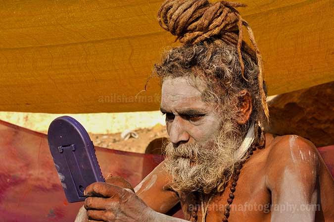 Culture- Naga Sadhu's (India) A Naga sadhu holding mirror in his hand at Varanasi ghat. by Anil Sharma Fotography