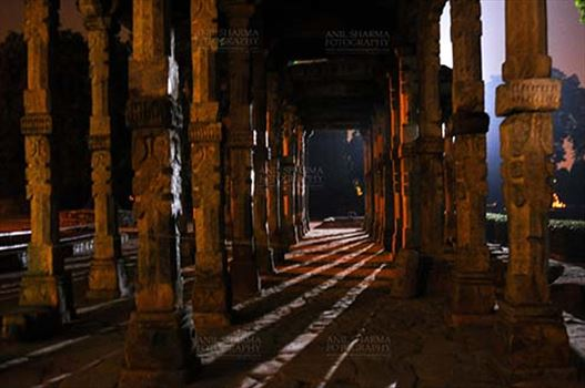 Monuments- Qutab Minar in Night, New Delhi, India. - The Beauty of Hindu Columns with stone carving at Quwwat-Ul-Islam mosque courtyard in night at Qutub Minar Complex, New Delhi, India.