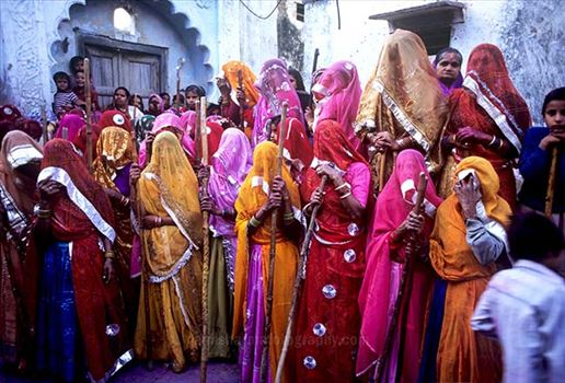 Festivals- Lathmaar Holi of Barsana (India) - women\u0027s wearing colorful saree\u0027s holding bamboo sticks during Lathmaar Holi at Barsana, Mathura, Uttar Pradesh, India.