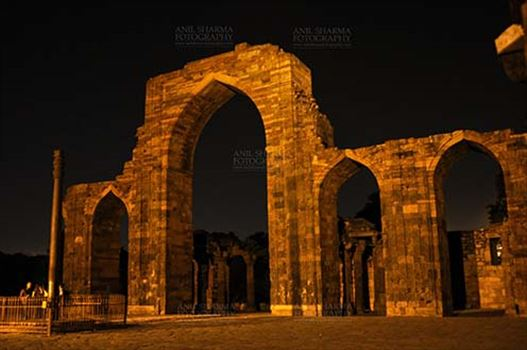 Monuments- Qutab Minar in Night, New Delhi, India. - The Beauty of arches of Iltutmish screen and some tourists standing near the iron pillar in night at Qutub Minar Complex, Mehrauli , New Delhi, India.