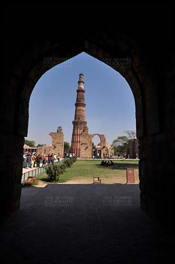 Monuments- Qutab Minar, New Delhi, India. - Qutub Minar the tallest brick minaret in the world seen through arch at Qutub Minar Complex, New Delhi, India.