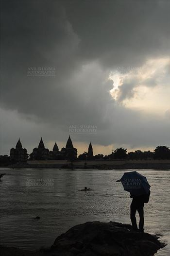 Monuments- Palaces and Temples of Orchha - DSC_0337 Orchha, Madhya Pradesh, India- August 20, 2012: Chhatris on the bank of river Betwa, a tourist holding umbrella enjoying cloudy- rainy weather at Orchha, Madhya Pradesh, India.