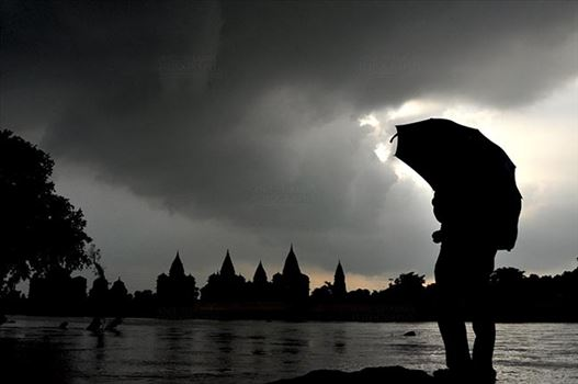 Monuments- Palaces and Temples of Orchha - Orchha, Madhya Pradesh, India- August 20, 2012: Chhatris on the bank of river Betwa, a tourist holding umbrella enjoying cloudy- rainy weather at Orchha, Madhya Pradesh, India.