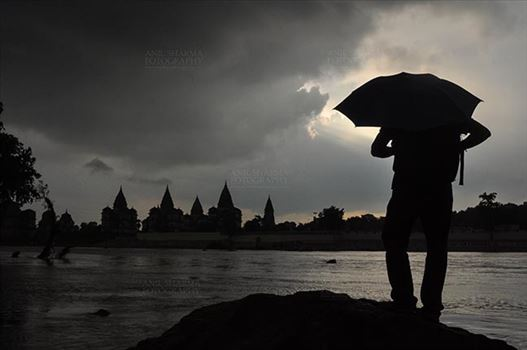 Monuments- Palaces and Temples of Orchha - Orchha, Madhya Pradesh, India- August 20, 2012: Chhatris on the bank of river Betwa, a tourist holding umbrella enjoying cloudy- rainy season at Orchha, Madhya Pradesh, India.