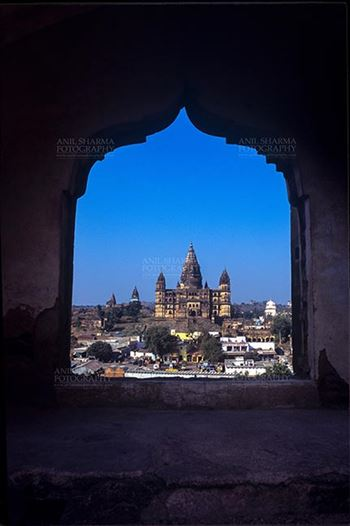 Monuments- Palaces and Temples of Orchha - Orchha, Madhya Pradesh, India- May 14, 2008: View from a carved window of Jahangir Mahal, Chaturbhuj temple is seen in the distance, Orchha, Madhya Pradesh, India.