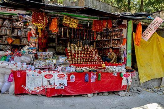 Travel- Gangotri (Uttarakhand) - Gangotri, Uttarakhand, India- May 13, 2015: A shopkeepers selling plastic bottles and devotional objects, for religious ceremonies at Gangotri, Uttarkashi, Uttarakhand, India.