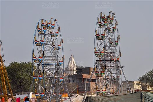 Fairs- Baneshwar Tribal Fair - Baneshwar, Dungarpur, Rajasthan, India- February 14, 2011: View of Baneshwar Mahadev temple standing between two ferris wheels at Baneshwar, Dungarpur, Rajasthan, India.