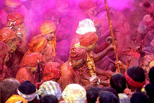 Festivals- Lathmaar Holi of Barsana (India) - People daubed in colored water, head covered singing a hymn during Lathmaar Holi celebrations at Barsana, Mathura, India.