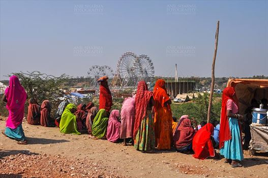 Fairs- Baneshwar Tribal Fair - Baneshwar, Dungarpur, Rajasthan, India- February 14, 2011: Bhil women in brightly coloured veils and saris enjoying panoramic view of the fair ground at Baneshwar Dungarpur, Rajasthan, India