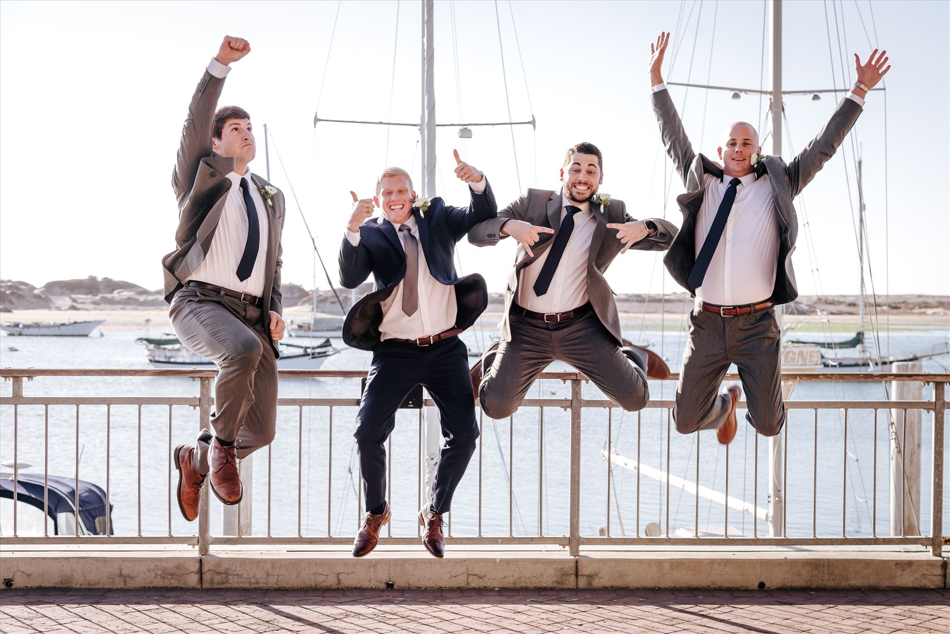 FW-9596.JPG Sarah Williams of Mirror's Edge Photography, a San Luis Obispo Wedding and Engagement Photographer, captures Ryan and Joanna's wedding at the iconic Windows on the Water Restaurant in Morro Bay, California.  Groomsmen jump in front of Morro Rock. by Sarah Williams