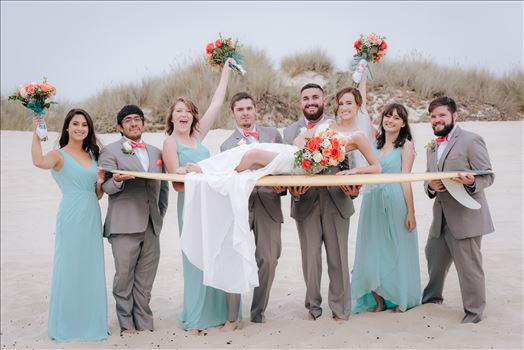 Sydney and Matthew 096 - Mirror\u0027s Edge Photography a San Luis Obispo Wedding Photographer captures Sydney and Matthew\u0027s Wedding on the Beach in Grover Beach, California. Bride, groom and bridal party having fun with surfboard on the beach in california wedding style