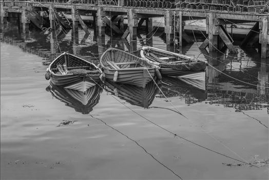 Tethered Boats Whitby 1, Edit; Duo-Tone - On a trip to Whitby in Yorkshire in 2012 and a walk through the town brought us to the harbour quay side and these small tethered boats, their bows and ropes reflected in the sea water and lobster pots neatly in stacks on the walkway. A \