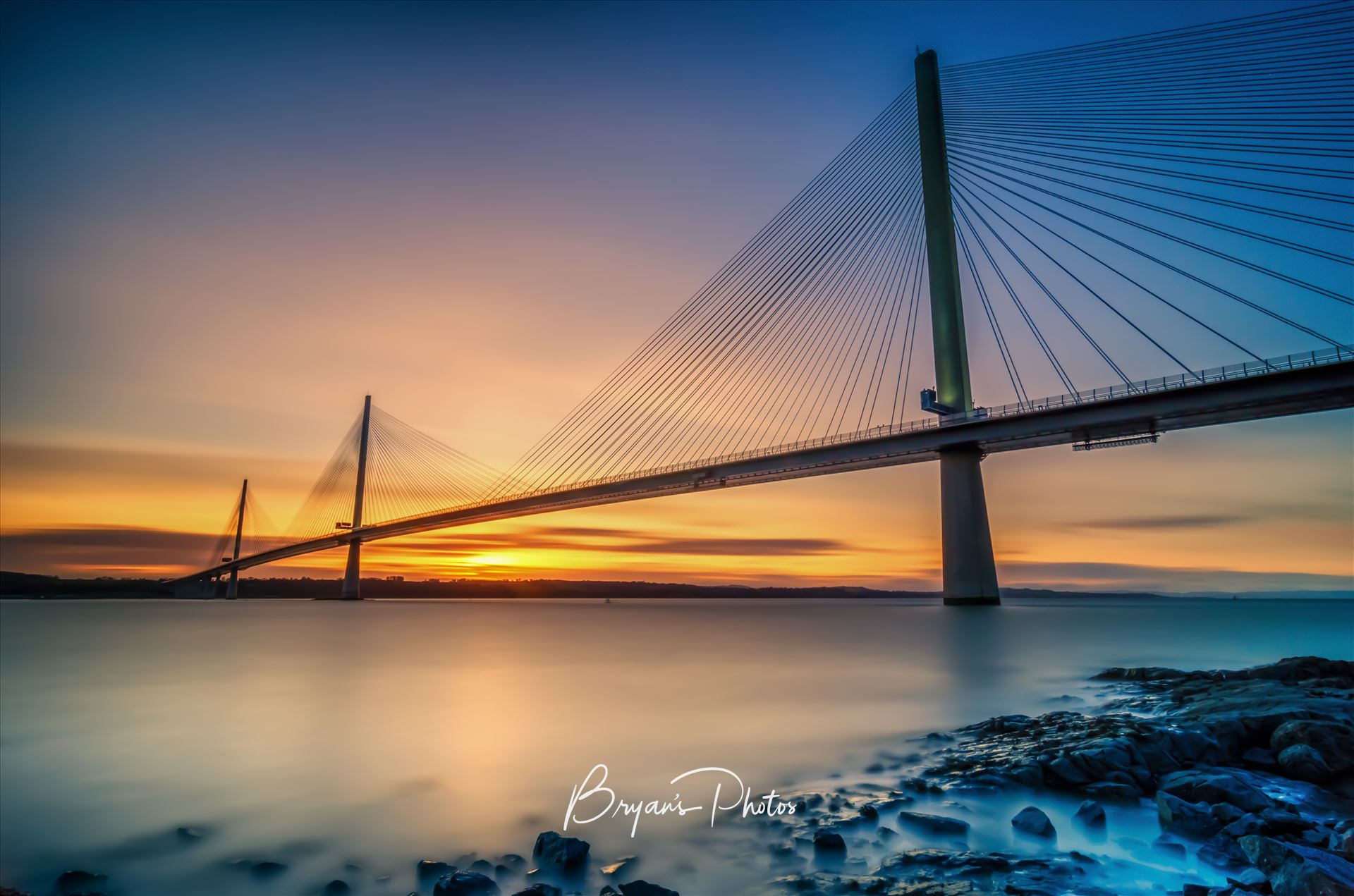 Queensferry Sunset A long exposure photograph of the Queensferry Crossing taken from North Queensferry on the Fife Coast. by Bryans Photos