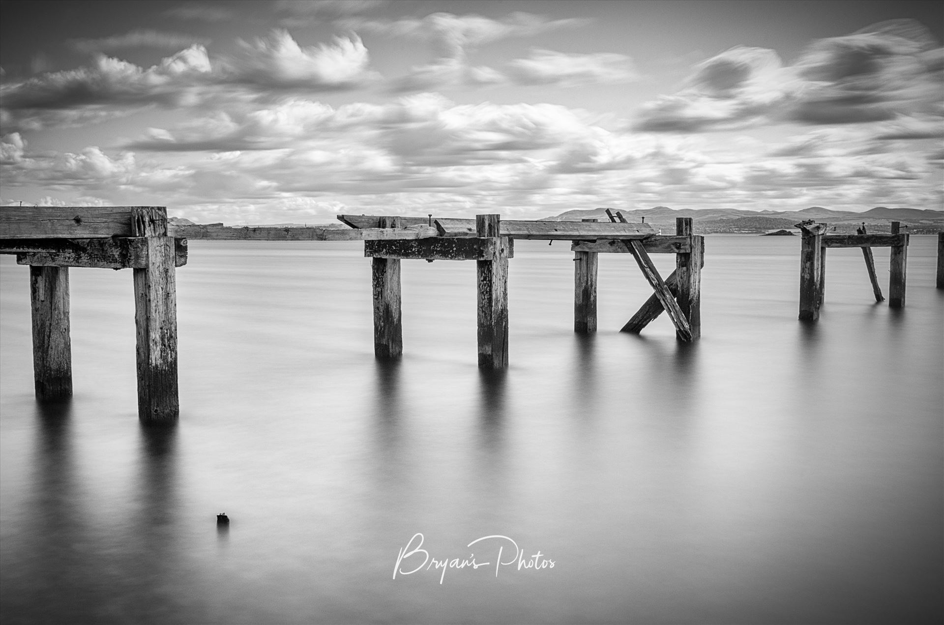 Aberdour A black and white photograph of the old abandoned pier at Aberdour on the Fife coast. by Bryans Photos