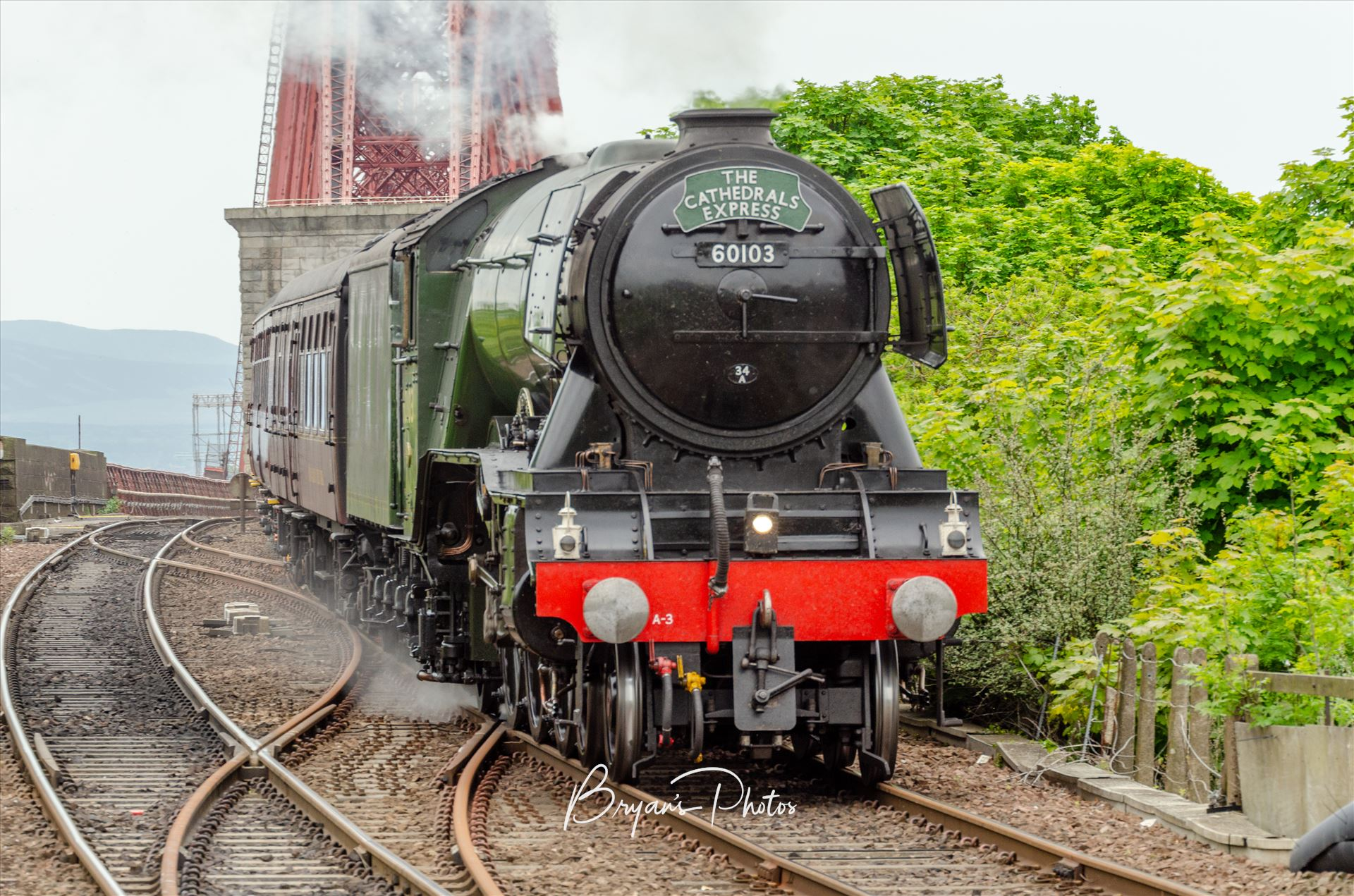 The Scotsman and the Bridge A photograph of the iconic Flying Scotsman steam engine as it approaches North Queensferry station with the Forth Rail Bridge in the background. by Bryans Photos