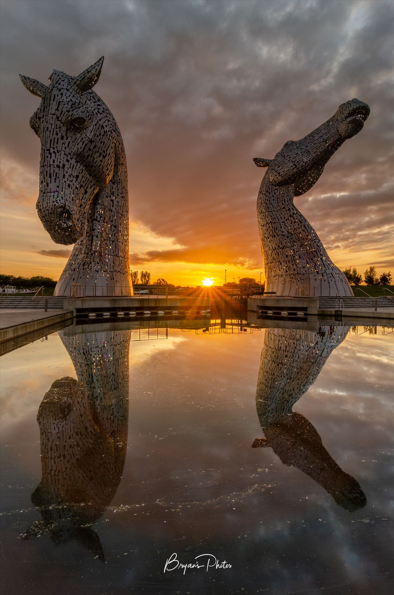 Sunset at the Kelpies A photograph of the Kelpies taken as the sun sets in between them. by Bryans Photos