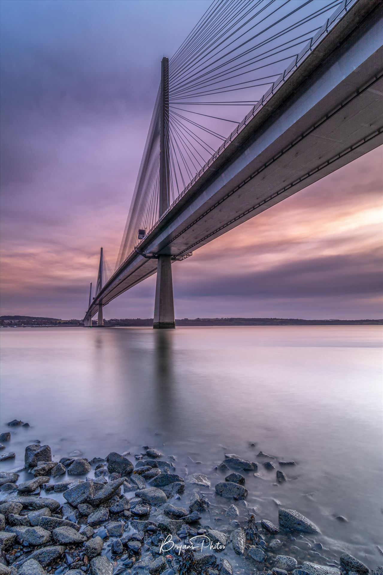 The Crossing A portrait photograph of the Queensferry Crossing taken from North Queensferry at sunset. by Bryans Photos