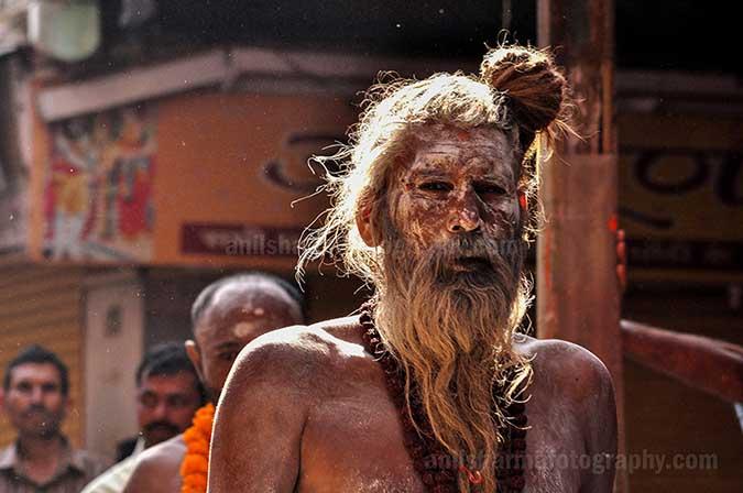 Culture- Naga Sadhu's (India) An old Naga Sadhu wearing Rudraksha beads mala passing through a small lane of Varanasi. by Anil Sharma Photography