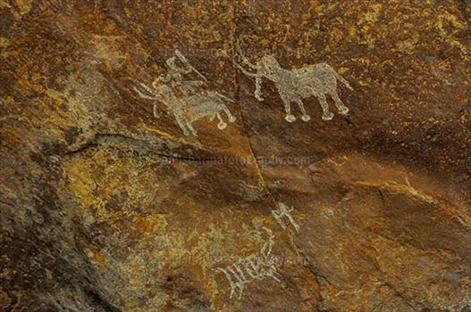 Archaeology- Bhimbetka Rock Shelters - Prehistoric rock painting of men with two Elephants at Bhimbetka archaeological site.